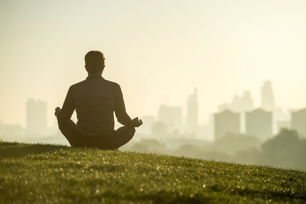 man sitting in the lotus position meditating on the grass