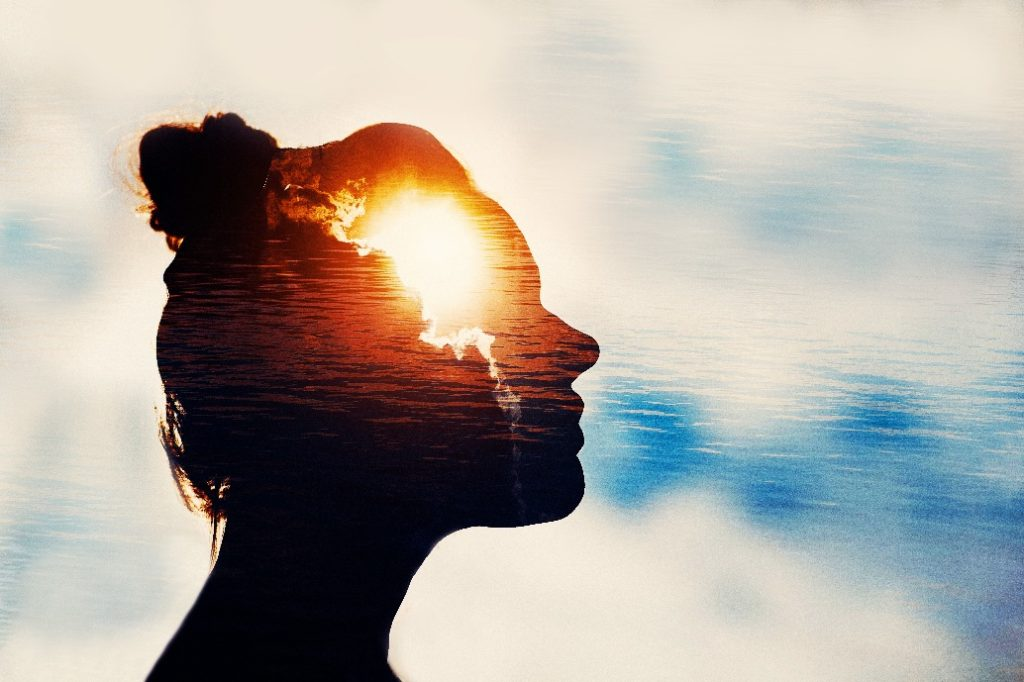 Sun behind clouds in silhouette of person's head