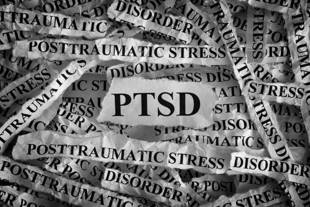 Torn pieces of paper with abbreviate PTSD. Posttraumatic stress disorder.