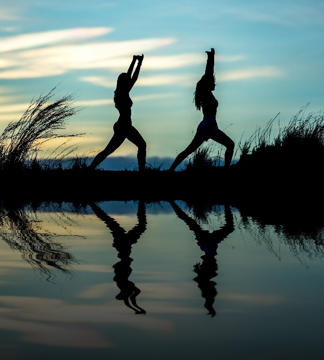 two women doing yoga exercise in front of a lake